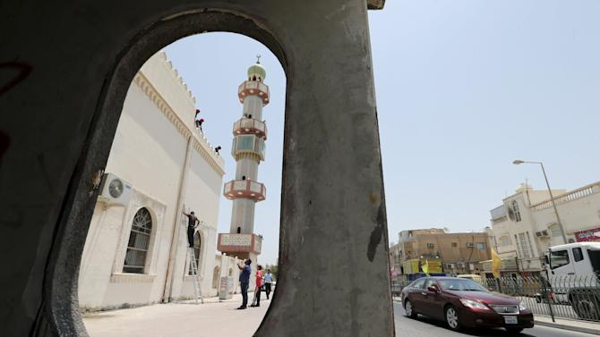 Workers install a security camera outside the Al A'ali Grand Mosque, ahead of Friday prayers in Al A'ali