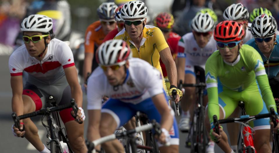 Competitors turn a corner during the men's road cycling race at the 2012 Summer Olympics, Saturday, July 28, 2012, in London. (AP Photo/Alastair Grant)