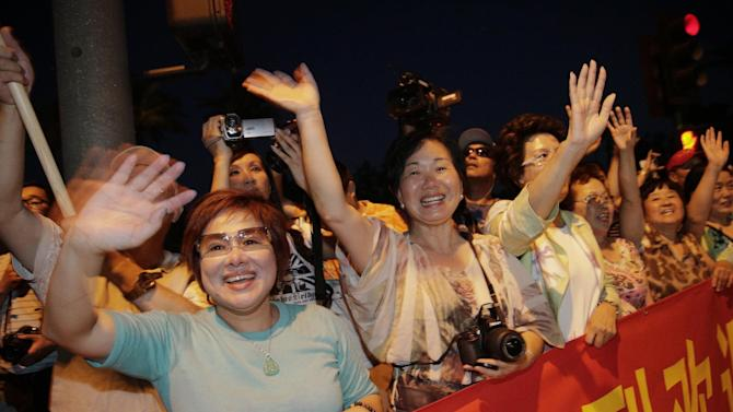 Supporters of Chinese President Xi Jinping cheer as they watch the motorcade carrying President Xi arrive in Indian Wells, Calif., Thursday, June 6, 2013. President Barack Obama and Chinese President Xi Jinping, seeking a fresh start to a complex relationship, are retreating to a sprawling desert estate for two days of talks on high-stakes issues, including cybersecurity and North Korea's nuclear threats. (AP Photo/Jae C. Hong)