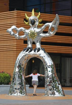 "This July 17, 2012 photo shows a woman walking through the ""Firebird"" sculpture in front of the Bechtler Museum of Art in downtown Charlotte, N.C. (AP Photo/Chuck Burton)"