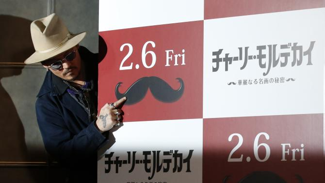 "Actor Johnny Depp jokes around during a photo session ahead of a news conference for his movie ""Mortdecai"" in Tokyo"