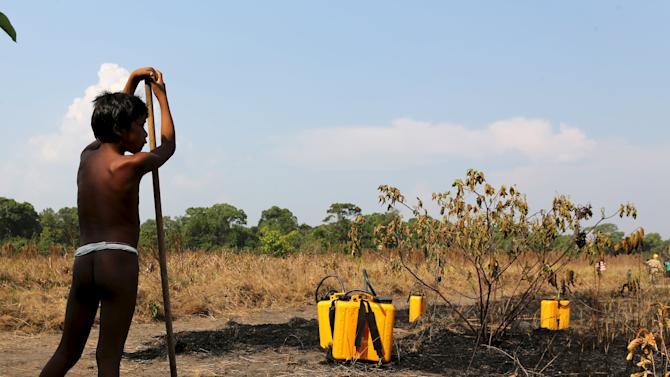 An indigenous boy stands next to equipment used to combat wildfire during a training at the Kamayura tribe, in the Xingu National Park, Mato Grosso, Brazil