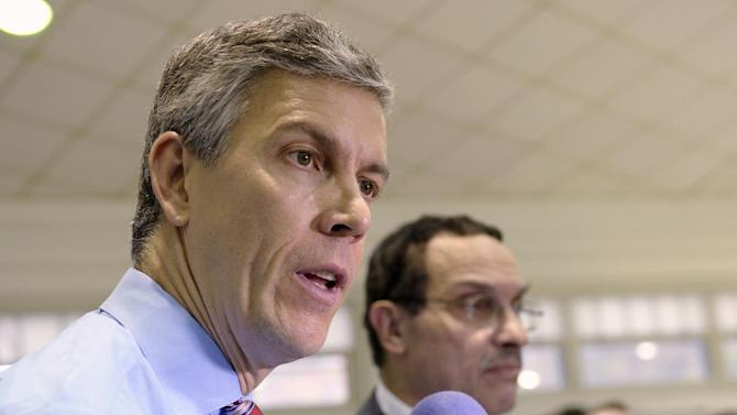 FILE - In this Nov. 7, 2013 file photo, Education Secretary Arne Duncan, left, speaks to reporters at Malcolm X Elementary School in Washington. Critics are relentless in warning about what they see as the folly of the new Common Core academic standards. The standards were written in private and never tested in real classrooms, they say. Educators aren't familiar enough with the standards to use them. They'll cost billions to put into place. Washington Mayor Vincent Gray is at right. (AP Photo/Susan Walsh, File)