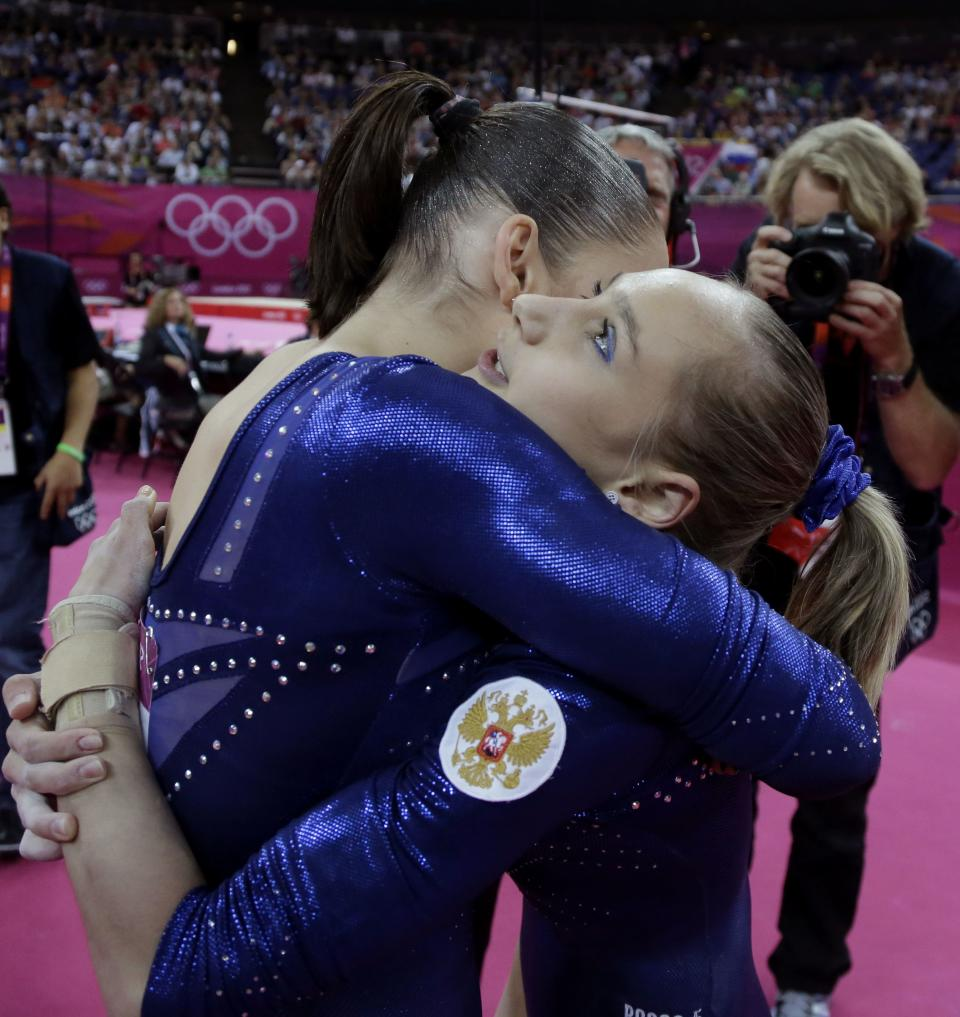 Russian gymnasts Aliya Mustafina, left, and Victoria Komova hug each other as they wait for the declaration of results during the artistic gymnastics women's individual all-around competition at the 2012 Summer Olympics, Thursday, Aug. 2, 2012, in London.  (AP Photo/Julie Jacobson)
