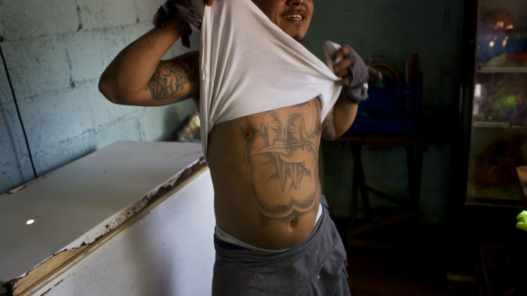 A member of the gang Mara Salvatrucha, MS, shows his tattoo inside the San Pedro Sula prison in Honduras, Tuesday, May 28, 2013. Honduras' largest and most dangerous street gangs have declared a truce, offering the government peace in exchange for rehabilitation and jobs. A Mara Salvatrucha gang spokesman says the gang and its rival, 18th Street, will commit to zero violence and zero crime in the streets as first step show of good faith. (AP Photo/Esteban Felix)