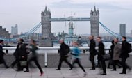 Commuters walk and jog across London Bridge in central London, on February 6, 2014, on the second day of a strike by London Underground workers