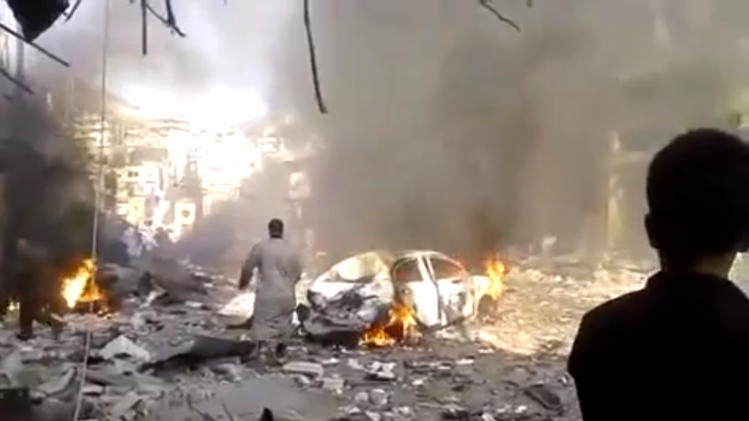 This image made from citizen journalist video posted by the Shaam News Network, which is consistent with other AP reporting, shows the aftermath of a car bomb attack on a market in the town of Darkoush in Idlib province, Monday, Oct. 14, 2013. Syrian activist groups say the bombing in a rebel-held northwestern town has killed and wounded dozens of people. Car bombs are becoming more common in Syria's civil war, now in its third year. The conflict has killed more than 100,000 people.(AP Photo/Shaam News Network via AP video)