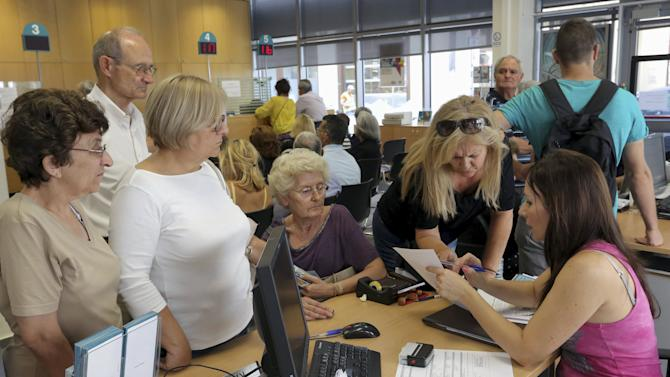An employee (R) of the National Bank informs pensioners inside a bank's branch in Iraklio on the island of Crete