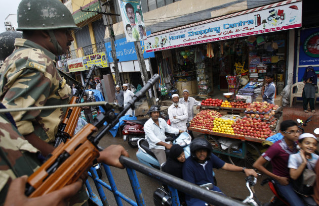 Indian paramilitary soldiers patrol the streets in Bangalore, India, Saturday, Aug. 18, 2012. Hundreds of Indians from the northeast are leaving the southern city of Bangalore