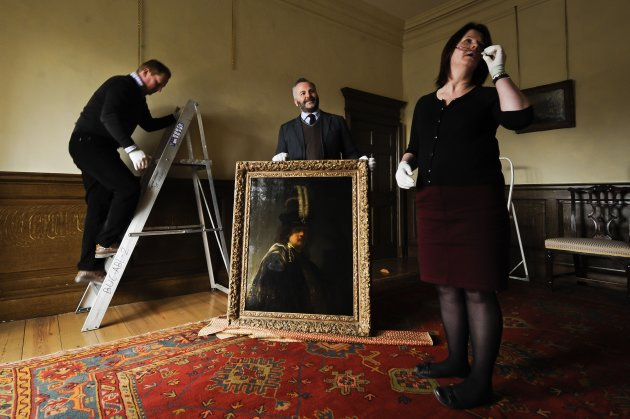 Buckland Abbey staff prepare to hang a recently confirmed self-portrait of Rembrandt, with Curator of Pictures and Sculpture David Taylor, centre, discovered at the Devonshire Abbey in Skipton, England, in this photo dated Wednesday March 13, 2013. The masterpiece was gifted in 2010 to Britain&#39;s National Trust by the family estate of a wealthy property developer, and has now undergone detailed investigations led by the world&#39;s leading Rembrandt expert, Ernst van de Wetering, to determine its provenance before declaring it an original painting by the Dutch master. The painting is now valued at 20 million pounds and will be hung at Buckland Abbey for a few months before being sent for cleaning and further expert analysis including x-ray and tree-ring dating of the beech panel it is painted on. (AP Photo/Ben Birchall, PA) UNITED KINGDOM OUT - NO SALES - NO ARCHIVES