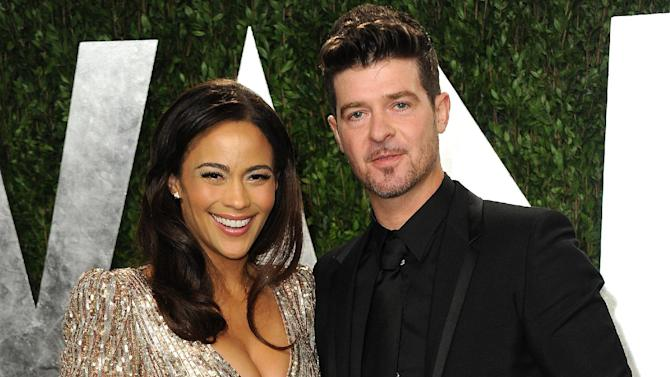 """FILE - In this Feb. 24, 2013 file photo, Paula Patton and Robin Thicke arrive at the 2013 Vanity Fair Oscars Viewing and After Party at the Sunset Plaza Hotel in West Hollywood, Calif. Thicke originally didn't plan to release the unrated version of his music video for the song """"Blurred Lines,"""" which features nude models prowling around him and rappers Pharrell and T.I. Thicke said his wife was OK with the models on the set and he sought her approval: """"Obviously if she didn't like it I wouldn't put it out."""" (Photo by Jordan Strauss/Invision/AP, File)"""