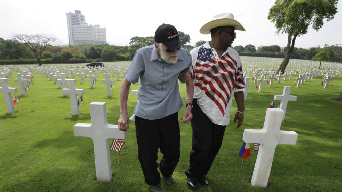 American Robert Dryfoos, left, from Conn., with Khalil Diallo walks around layers of tombs after attending Memorial Day rites at the American Cemetery in suburban Taguig, south of Manila, Philippines on Sunday May 27, 2012. The cemetery site contains the largest number of U.S. military dead of World War II. (AP Photo/Aaron Favila)