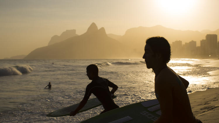 This Sept. 5, 2012 photo shows skimboarders running to the water at Ipanema beach in Rio de Janeiro, Brazil. Rio boasts some of the world's most stunning urban beaches and they're worth several visits. (AP Photo/Felipe Dana)