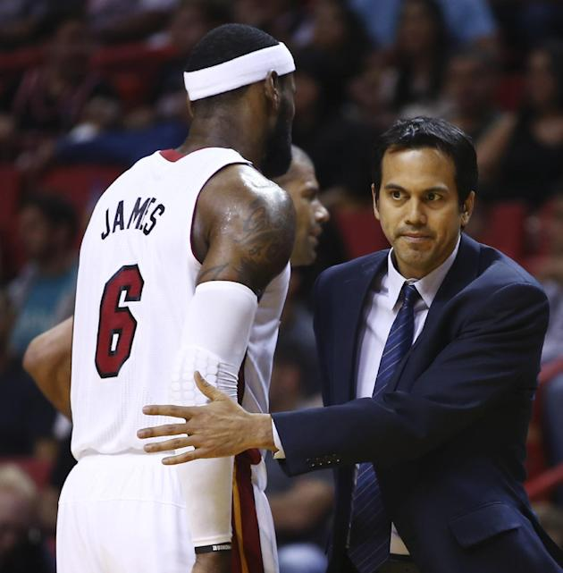Miami Heat's LeBron James (6) walks past coach Erik Spoelstra after James was charged with an offensive foul against the Washington Wizards during the first half of an NBA  basketball game, Monday