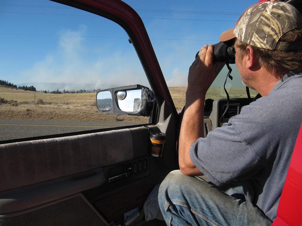John Thometz monitors the progress of a wildfire Aug. 14, 2012 near his Cle Elum, Wash. home. The fire has destroyed dozens of homes. (AP Photo/Shannon Dininny)