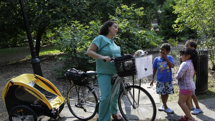 This Aug. 9, 2012 photo shows Dr. Elisabeth Coletti, a Brooklyn-based veterinarian who makes house calls, commuting to an appointment with her own pet, Milo, a Cocker Spaniel, in the front basket of her bicycle as she stops to chat with some youngsters in Prospect Park en route in New York.  (AP Photo/Kathy Willens)