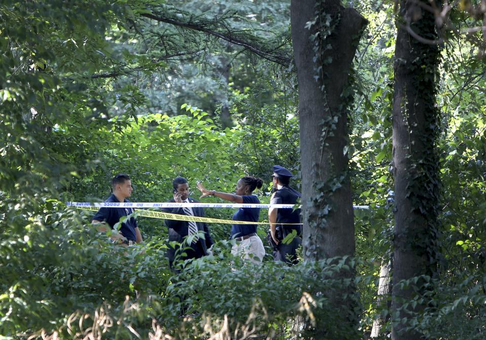 Police officers talk near a crime scene in a heavily wooded section of Central Park in New York, Wednesday, Sept. 12, 2012. Police say a woman in her 70s has reported that she was sexually assaulted in Central Park. (AP Photo/Seth Wenig)