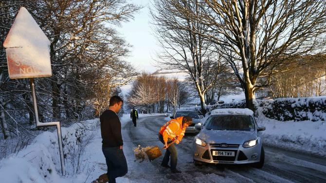 A man digs out snow from under a car struggling to climb a hill on the A515 near Ashbourne