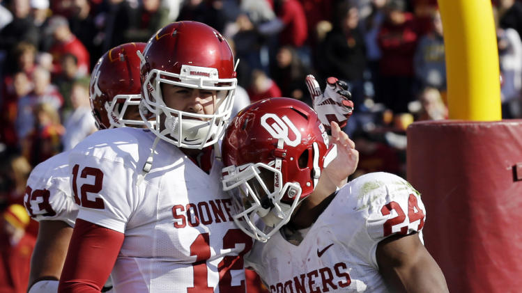 Oklahoma running back Brennan Clay, right, celebrates with quarterback Landry Jones after scoring on an 18-yard touchdown run during the second half of an NCAA college football game against Iowa State, Saturday, Nov. 3, 2012, in Ames, Iowa. Oklahoma won 35-20. (AP Photo/Charlie Neibergall)