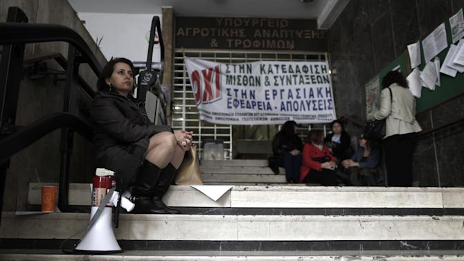 "Agriculture ministry workers are seen at the entrance to the ministry headquarters in Athens, which was occupied by protesting employees on Monday, Nov. 19, 2012. The banner reads ""No to the demolition of salaries and pensions."" Civil service unions are up in arms over government plans to place 2,000 state employees on notice ahead of reassignment or potential dismissal. (AP Photo/Petros Giannakouris)"