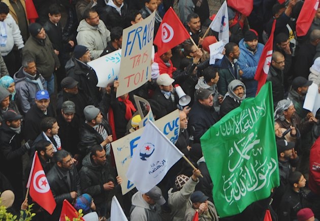 "Protesters gather during a demonstration in Tunis Saturday Feb 9, 2013. Several thousand supporters of Tunisia's ruling moderate Islamist party rallied in the capital in a pro-government demonstration Saturday, a day after the funeral of an assassinated opposition politician. The ruling Ennahda party had called for a show of support for the constitutional assembly, whose work on a new constitution suffered a severe setback after the killing of Chokri Belaid on Feb. 6, 2013 when leftist parties withdrew their participation. Protesters hurled insults at France, accusing the former colonial ruler of interfering in the North African country's politics. banners, center, is read ""France shut up"" ( Ap Photo/Hassene Dridi)"