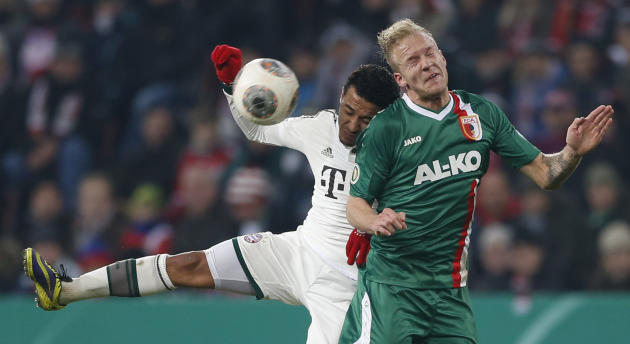 Augsburg's Kevin Vogt, right, and Bayern's Thiago Alcantara of Spain challenge for the ball during the German soccer cup third round match between FC Augsburg and FC Bayern Munich in Augsburg,