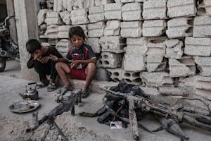 Children look at seized weapons from the Islamic State…