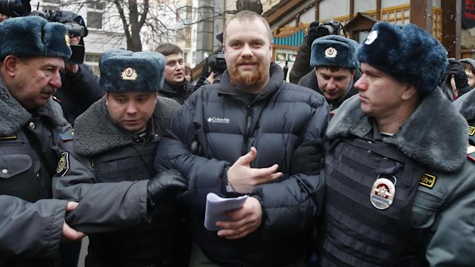 Police officers detain Dmitry Demushkin, the leader of the banned ultra-nationalist group Slavic Union, outside a court where Russian martial arts champion Rasul Mirzaev was found guilty of involuntary manslaughter, Moscow, Russia, Tuesday, Nov. 27, 2012. Mirzayev was sentenced to two years of house arrest over the death of a man he had punched outside a club. (AP Photo/Misha Japaridze)