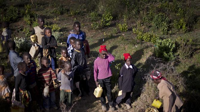 In this Saturday Feb. 9, 2013 photo, displaced boys holding empty plastic containers gather to fill them with water from a muddy borehole in the ground, at 'Hope' camp for internally-displaced Kenyans from the Kikuyu tribe, near Nyahururu, in Kenya.  The 624 people living at Hope Camp, a spot near the equator in a placed called Laikipia, is an illustration of one of the many lingering effects of the tribe-on-tribe violence that rocked Kenya after its 2007 presidential election. Five years later _ and now only days before the country's March 4 presidential election _ hundreds of refugees still have not returned home. (AP Photo/Ben Curtis)