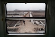 North Koreans are seen from the window of a train along the railway line between Pyongyang and the North Phyongan Province. North Korea is hardly known for offering a warm welcome to the world's press, and never before has it given access to a sensitive site featuring its latest space hardware