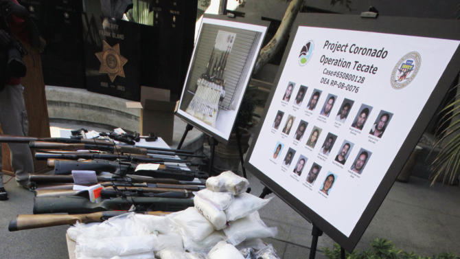 FILE - In this Oct. 22, 2009 file photo, weapons and drugs seized in special joint operation conducted with the Drug Enforecement Administration against the La Familia drug cartel based out of Michoacan, Mexico and operating in San Bernardino and surrounding counties, are on display at a news conference at sheriff's headquarters in San Bernardino, Calif. Drug cartels have long been the nation's No. 1 supplier of illegal drugs, but in the past, their operatives rarely ventured beyond the border. A wide-ranging Associated Press review of federal court cases and government drug-enforcement data, plus interviews with many top law enforcement officials, indicate the groups have begun deploying agents from their inner circles to the U.S. (AP Photo/Reed Saxon, File)
