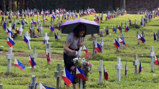 A woman places a candle in front of a tombstone decorated with flowers at a military camp in Taguig City