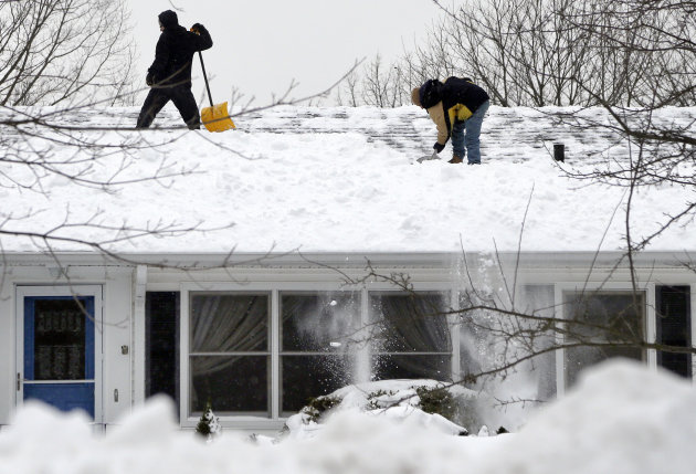 Two men clear snow off a roof of a home in North Andover, Mass. Monday, Feb. 11, 2013. Beleaguered Massachusetts residents returned to work on Monday for the first time since the weekend blizzard, cra