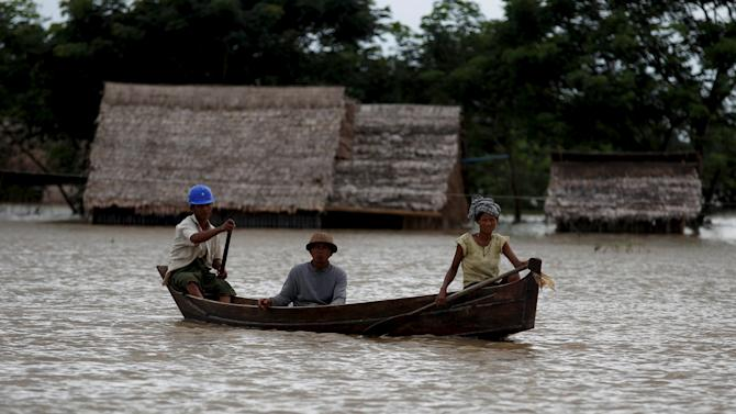 File photo of people travelling in their boat as they pass near flooded homes in Zalun