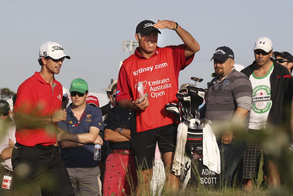 Australia's Adam Scott, left, and caddie Steve Williams plan the shot out of the rough on the 10th fairway during the second round of the Australian Open golf tournament in Sydney, Australia, Friday, Nov. 11, 2011. (AP Photo/Rob Griffith)