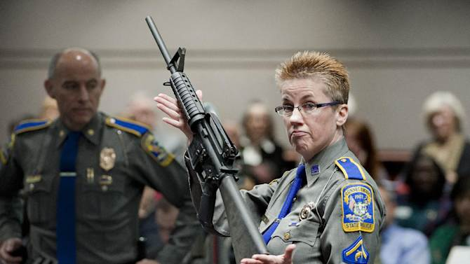 Firearms Training Unit Detective Barbara J. Mattson of the Connecticut State Police holds up a Bushmaster AR-15 rifle, the same make and model of gun used by Adam Lanza in the Sandy Hook School shooting, for a demonstration during a hearing of a legislative subcommittee reviewing gun laws, at the Legislative Office Building in Hartford, Conn., Monday, Jan. 28, 2013. The parents of children killed in the Newtown school shooting called for better enforcement of gun laws Monday at the legislative hearing. (AP Photo/Jessica Hill)