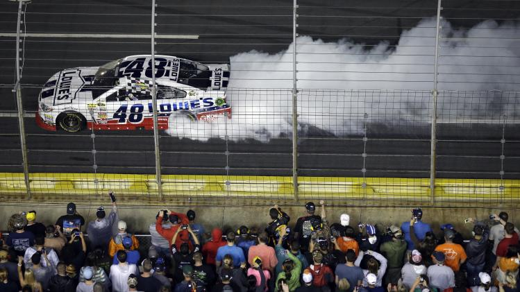 Jimmie Johnson (48) does a burnout after winning the NASCAR Sprint Cup Series All-Star auto race at Charlotte Motor Speedway in Concord, N.C., Saturday, May 18, 2013. (AP Photo/Gerry Broome)