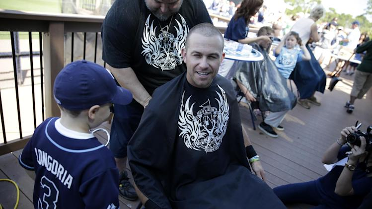 Tampa Bay Rays third baseman Evan Longoria gets his hair cut by cancer patient Josh Fischer, 5, of Odessa, Fla., before an exhibition baseball game against the Boston Red Sox in Port Charlotte, Fla., Sunday, March 16, 2014. The event was a fundraiser for the Pediatric Cancer Foundation. (AP Photo/Gerald Herbert)