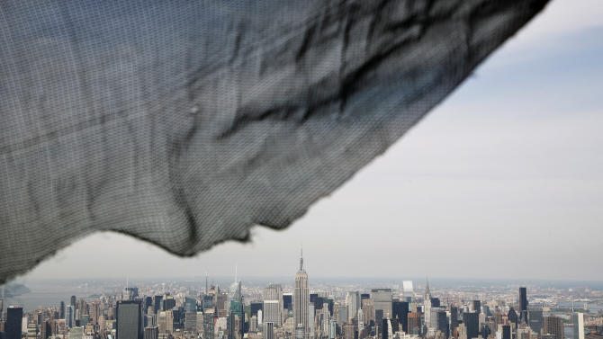A torn safety net on One World Trade Center provides a window view of the Manhattan skyline, Monday, April 30, 2012 in New York. One World Trade Center is being built to replace the twin towers destroyed in the Sept. 11 attacks. It reached just over 1,250 feet on Monday. That's just taller than the observation deck on the Empire State Building. (AP Photo/Mark Lennihan, Pool)