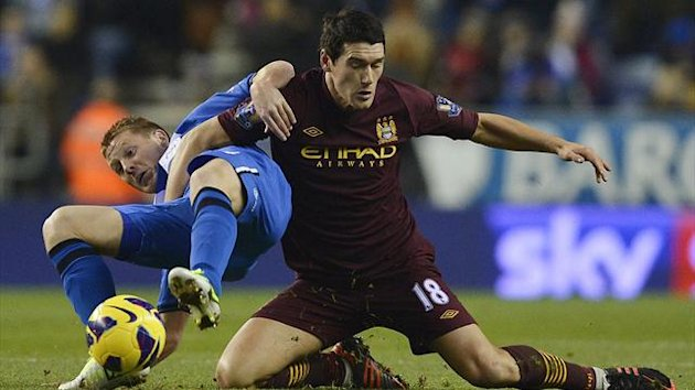 Wigan Athletic's James McCarthy (L) challenges Manchester City's Gareth Barry during their English Premier League match
