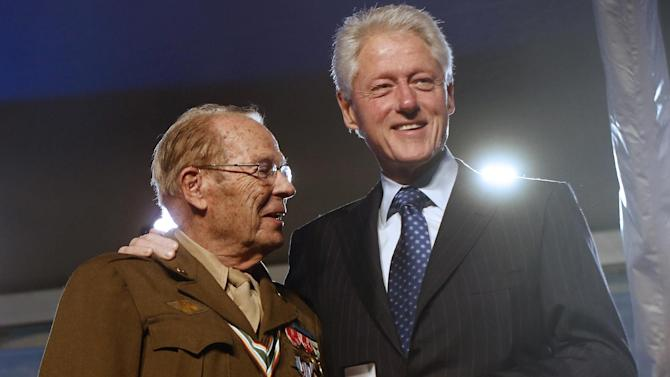 Former President Bill Clinton, right, presents World War II Army veteran Scottie Ooton, a member of the 84th Infantry Division which liberated Hannover-Ahlem concentration camp, with for the 20th anniversary pin of the United States Holocaust Memorial Museum in Washington, Monday, April 29, 2013. (AP Photo/Charles Dharapak)
