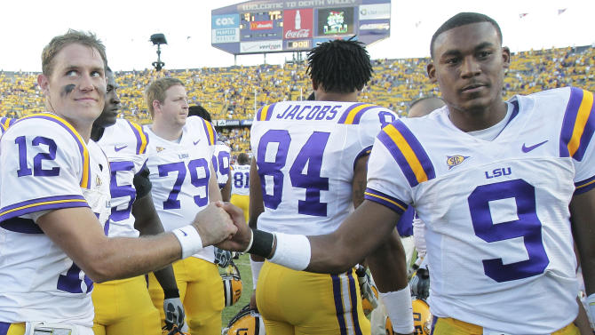 LSU quarterbacks Jarrett Lee (12) and  Jordan Jefferson (9) congratulate each other after defeating Florida 41-11 in an NCAA college football game in Baton Rouge, La., Saturday, Oct.  8, 2011. (AP Photo/Bill Haber)