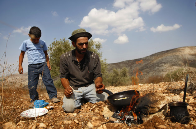 In this photograph made on Monday, Oct. 22, 2012, a Palestinian farmer Khader Khader, 31, cooks food on his land in Nisf Jubeil, near the West Bank city of Nablus. In an emerging back-to-the-land movement, Palestinian farmers are turning the rocky hills of the West Bank into organic olive groves, selling their oil to high-end grocers in the U.S. and Europe. (AP Photo/Majdi Mohammed).