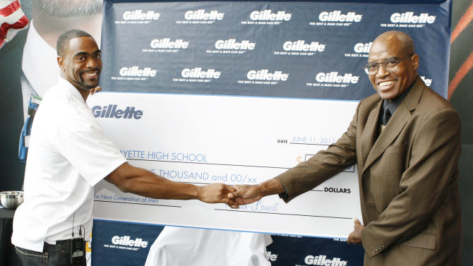 COMMERCIAL IMAGE - American 100m record holder Tyson Gay, left, shakes hands with his former high school coach Ken Northington after presenting him with a $25,000 Great Start grant to support the next generation of men at Gillette World Shaving Headquarters, Monday, June 11, 2012, in Boston. The grant will support the track and field team at Lafayette High School in Lexington, KY., where Gay got his great start. (Photo by Bizuayehu Tesfaye/Invision for Gillette/AP Images)