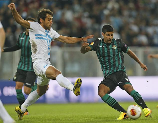 Betis' Juanfran, right, is challenged by Rijeka's Mate Males, during their group I Europa League first round second leg soccer match, at Kantrida stadium in Rijeka, Croatia, Thursday, Oct. 3, 2013