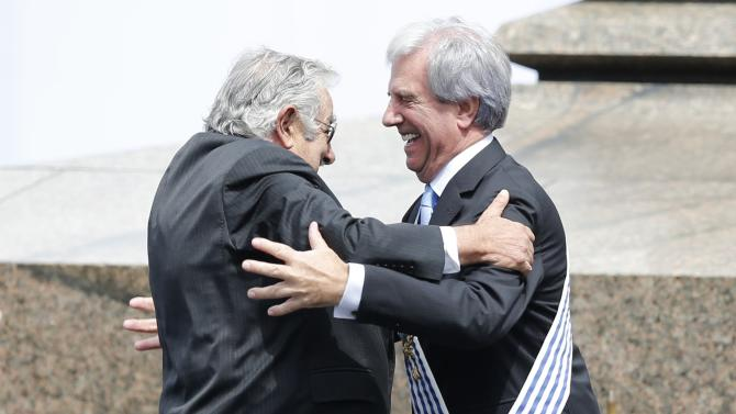 Uruguay's outgoing president Mujica and incoming president Vazquez hug after Mujica handed over the presidential sash in Montevideo