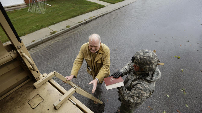 "Maryland National Guard Sgt. Zachary Greene holds a bible for Harold ""Doc"" Sterling as he prepares to climb the ladder into a National Guard truck to be evacuated from his home after the effects of superstorm Sandy Tuesday, Oct. 30, 2012, in Crisfield, Md. (AP Photo/Alex Brandon)"