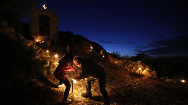 A girl watches as her grandfather tries to light a candle on the hill leading up to Laferla Cross outside the village of Siggiewi, southwest of Valletta