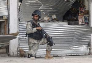 An Afghan security force takes up position at the site of an attack in Jalalabad