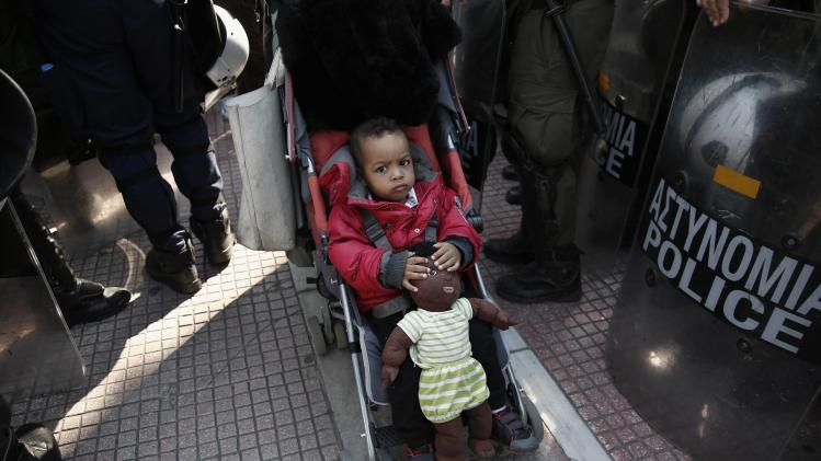 A child holds a soft toy as he makes his way through policemen who are securing a protest rally in Athens